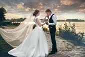 The Bride And Groom In Wedding Dresses On Natural Background.the Stunning Young Couple Is Incredibly poster