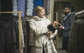 Man With Strict Face And Woman With Coats In Fur Shop. Money And Style Concept. Woman In Fur Coat Wi poster