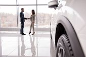 Wide Angle Portrait Of Car Salesman Shaking Hands With Woman Buying New Car In Dealership Showroom,  poster
