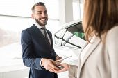 Portrait Of Handsome Car Salesman Giving Car Keys To Young Woman Standing Next To White Shiny Luxury poster