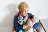 Happy Grandmother Holding Newborn Baby Grandchild On Arms In Hospital. Proud Senior Woman With Cute  poster