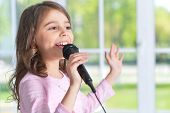 Beautiful Little Girl With Microphone At Home poster