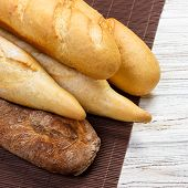 Assortment Of Fresh French Baguettes On A Wooden Table. poster