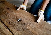 Carpenter man installing wooden floor poster