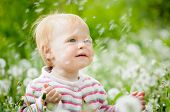 stock photo of defloration  - Outdoor portrait of a cute little baby in the grass