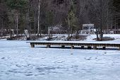 Pier On The Lake. Wooden Bridge In Forest In Winter Time With Blue Frozen Lake. Lake For Fishing Wit poster