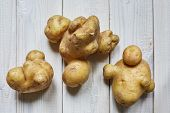 Several Ugly Potatoes On A Wooden Background. The Concept Of Store Rejection Of Ugly Food. Non-gmo O poster
