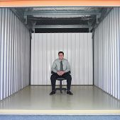 picture of self-storage  - Businessman sitting in empty storage space - JPG