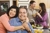 Middle-aged Hispanic couple hugging at party
