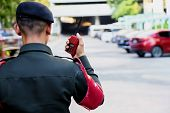 Security Guard Uses Radio Communication For Facilitate Traffic. Traffic Officers Use Walkie Talkie T poster