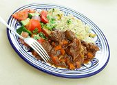 stock photo of tagine  - A beef tagine stew meal served with rice cooked with nuts and spices and a tossed salad of tomato - JPG