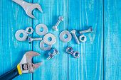 Metal Bolts And Nuts On Blue Wooden Background With Adjustable Wrench poster