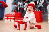 Charming Toddler Boy Holds White Christmas Gift Box With Red Ribbon. Funny Cute Baby Weared In Festi poster
