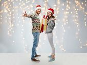 people and holidays concept - happy couple in santa hats with christmas gifts at ugly sweater party  poster