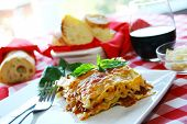 image of lasagna  - Lasagna on a white plate decorate with basil and serve with bread and red wine - JPG