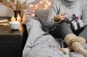 Woman Holding Gift In Cozy Room. Cold Day In Warm House. Concept Hygge. Merry Christmas! poster