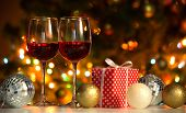 Crystal glasses of wine and Christmas balls and Christmas gifts on the background of Christmas light poster