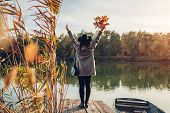 Woman Walking On Lake Pier By Boat Raising Hands And Admiring Autumn Landscape. Fall Season Activiti poster