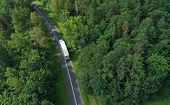Aerial Drone Perspective View On White Truck With Cargo Trailer Riding Through The Forest On Curved  poster
