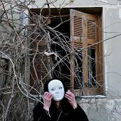 stock photo of grotesque  - Grotesque white mask figure and haunted house window with tangled overgrown plants and creepy dummy doll hand - JPG