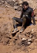 POCONO MANOR, PA - APR 29: A man sits on the banks before entering a mud pit at Tough Mudder on Apri
