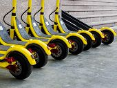Several Yellow E-scooters Stand In A Row For Rent. Scooters Are Available For Rent. Walk Around The  poster