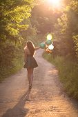 Beautiful Brunette Girl In Glamorous Green Dress Walking Down The Road Holding Colorful Balloons. Re poster
