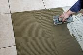 stock photo of mortar-joint  - A man on his knees installing a ceramic tile floor - JPG