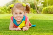 Picture of cute little girl lying down on green grass in park, cheerful child resting on the field o