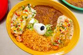 stock photo of enchiladas  - Enchiladas and rice and beans at a Mexican restaurant serving authentic cuisine - JPG