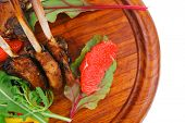 main portion : grilled ribs on woden plate isolated over white background with salad leaves and red