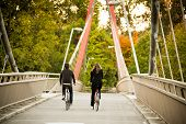 stock photo of bike path  - A man and woman ride their bikes together along a bike path bridge - JPG