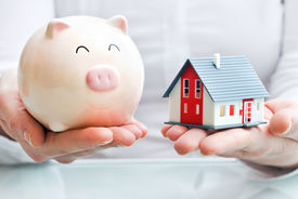 foto of possession  - Hands holding a piggy bank and a house model - JPG