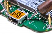 image of electric socket  - Electronic technician repairs mini USB socket on mobile phone circuit board - JPG