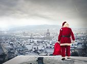 stock photo of red roof  - Santa Claus over the city with red sack - JPG