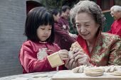 image of medium-  length hair  - Grandmother and granddaughter making dumplings in traditional clothing - JPG