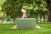 Young woman lying on grass in front of laptop at the park