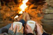 Close-up of hands holding coffee cups in front of lit fireplace