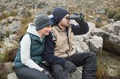 Side view of a young couple sitting on rock with binoculars while on a hike