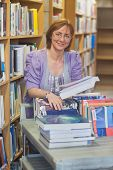 pic of librarian  - Content calm female librarian returning books smiling at camera - JPG