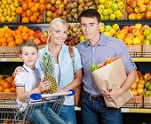 Family against shelves of fruits goes shopping. Father keeps a paper bag with fruits and vegetables,