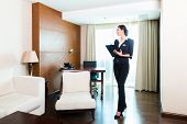 stock photo of housekeeping  - Asian Chinese Housekeeping manager or assistant controlling or checking the room or suit of a hotel with a checklist on tidiness - JPG