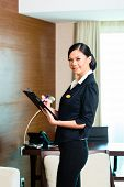 Asian Chinese Housekeeping manager or assistant controlling or checking the room or suit of a hotel