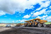 stock photo of dumper  - big truck in open pit and blue sky at mae moh Mine THAILAND - JPG