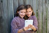 picture of siamese  - twin girls fancy dressed up pretending be siamese with dad shirt playing with tablet pc - JPG