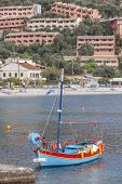 Kalami bay, Corfu, with new holiday villas on the cliff and a traditional fishing boat moored in the