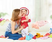 stock photo of dowry  - Happy Mother and baby girl with clothes ready for traveling on vacation - JPG