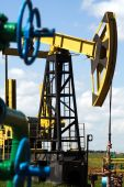 stock photo of nonrenewable  - Oilfield Pump Jack with a bright blue sky and clouds - JPG