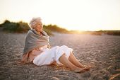 stock photo of beautiful senior woman  - Image of relaxed elderly woman sitting on the beach looking at a view - JPG