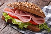 stock photo of tomato sandwich  - Sandwich with ham lettuce and tomatoes on an old table - JPG